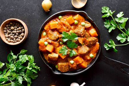 Beef stew with potatoes and carrots in tomato sauce on black background.  Top view, flat lay Stock Photo