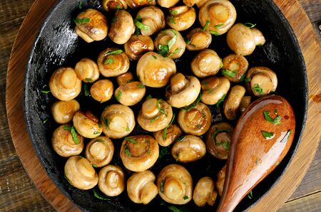Fried mushrooms in frying pan. Top view, flat lay