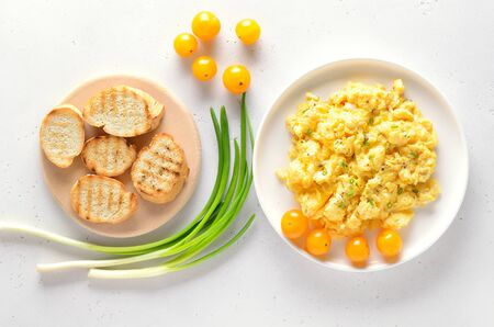 Scrambled eggs and tomatoes over white stone background. Top view, flat lay