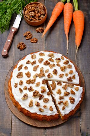 Carrot cake on wooden background. Walnut and fresh carrots on the table