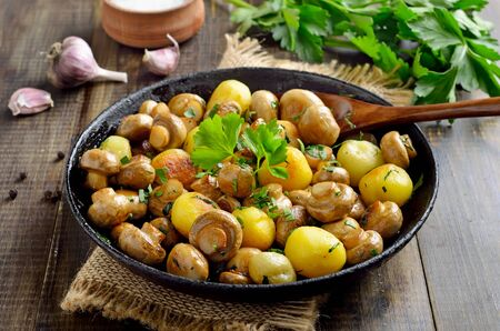 Fried mushrooms with potatoes in cast iron pan on wooden table