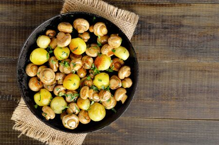 Delicious fried mushrooms and potatoes in frying pan on wooden background with copy space. Top view, flat lay