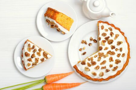 Homemade carrot cake with icing decorated walnut on white plate. Top view, flat lay