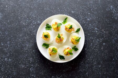 Stuffed eggs with egg yolk, bacon, mustard and parsley on dark stone background with copy space. Top view, flat lay Stock Photo