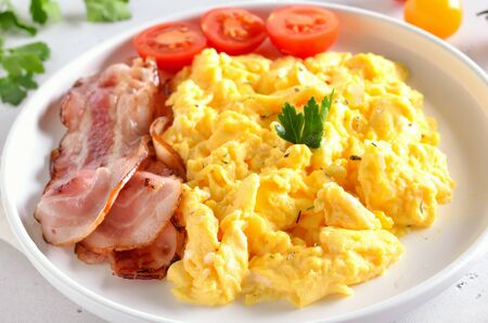 Scrambled eggs, fried bacon and tomatoes on white plate, close up view