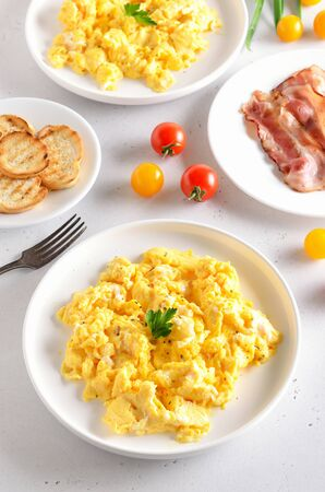 Scrambled eggs. Fried bacon and tomatoes on white plate.  Healthy diet breakfast concept Stock Photo