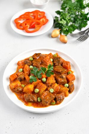 Beef stew with potatoes and carrots in tomato sauce on white plate