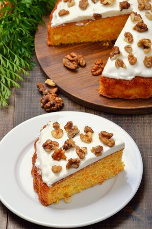 Piece of carrot cake with icing decorated walnut on white plate, close up view