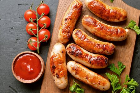 Grilled sausages on a cutting board, sause and cherry tomatoes on black stone background. Top view, flat lay Stock Photo - 144994760