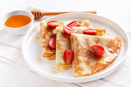 Homemade thin pancakes with strawberry slices and honey on white plate, close up view