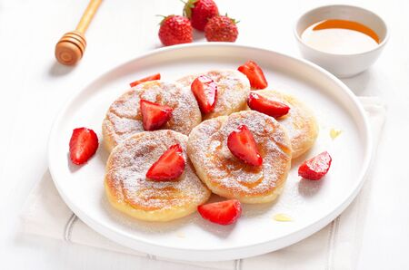 Homemade pancakes with cottage cheese and strawberry slices, syrniki, close up view