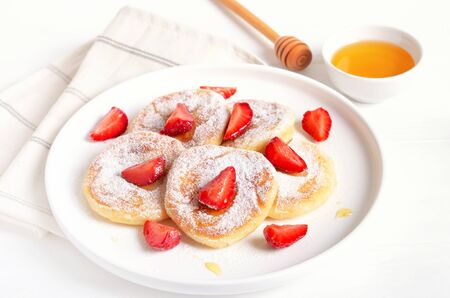 Homemade pancakes with cottage cheese and strawberry slices. Healthy breakfast, close up view