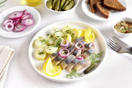 Sliced herring fish with boiled potatoes on white plate. Russian cuisine Stock Photo