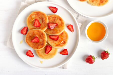 Cottage cheese pancakes with strawberry slices and honey. Healthy breakfast. Top view, flat lay