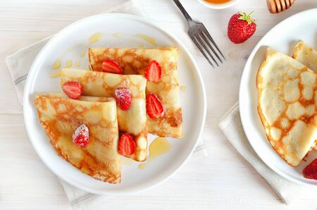 Homemade thin pancakes with strawberry slices and honey on table.  Top view, flat lay Stock Photo