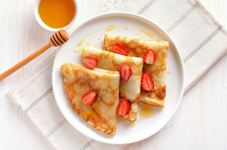 Homemade crepes with strawberry slices and honey. Top view, flat lay Stock Photo - 147335907