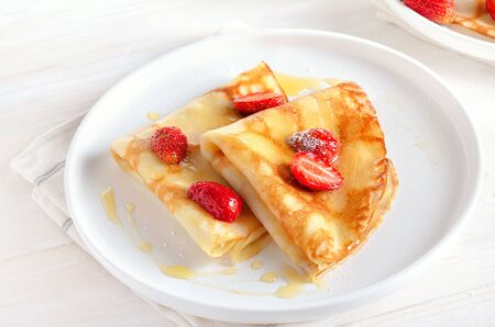 Homemade thin pancakes with strawberry slices and honey on white plate, close up view Stock Photo - 147335916