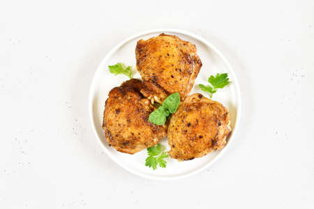 Fried chicken thighs in plate on white stone background with copy space. Top view, flat lay Stock Photo