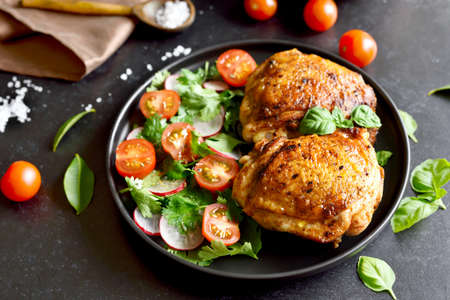 Fried chicken thighs with vegetables in plate