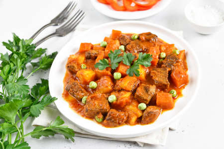 Beef stew with potatoes and carrots in tomato sauce on white plate, close up view