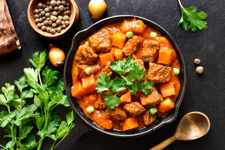 Beef stew with potatoes in tomato sauce on black stone background. Top view, flat lay Stock Photo - 152490159