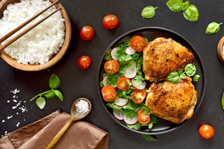 Fried chicken thighs with vegetables in plate and bowl of rice over black stone background. Top view, flat lay Stock Photo