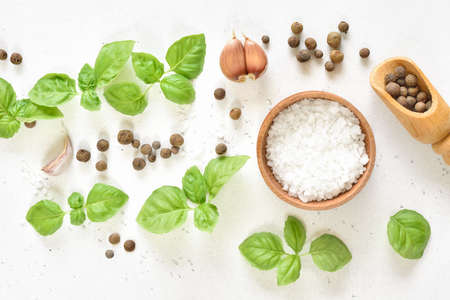 Fresh basil and spices on light stone background. Top view, flat lay
