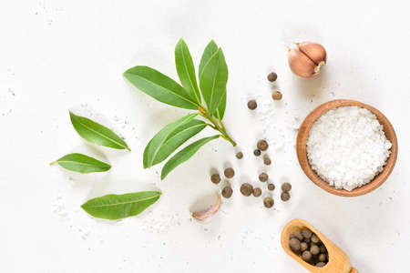 Fresh bay leaf, allspice and garlic on white stone background. Top view, flat lay Stock Photo