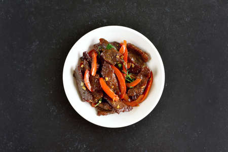 Thai beef stir-fry in bowl on dark stone background with copy space. Top view, flat lay Stock Photo - 152490165