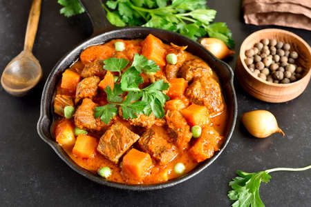 Beef stew with potatoes and carrots in tomato sauce in frying pan, close up view