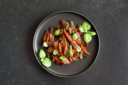 Thai style stir-fry beef with vegetables on plate over dark stone background. Top view, flat lay Stock Photo