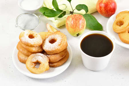 Apple rings on white plate, cup of black coffee on white stone background
