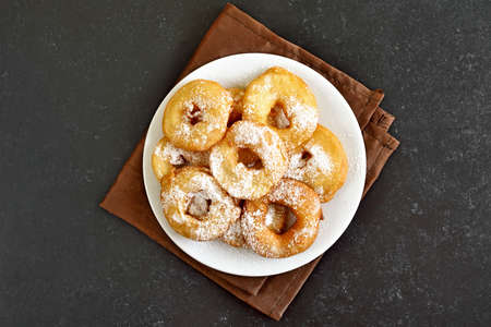 Homemade donuts on white plate over dark stone background. Top view, flat lay