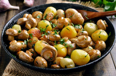 Fried mushrooms and potatoes in frying pan, close up view