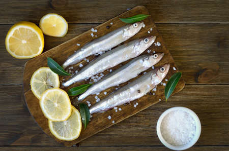 Raw fish (smelt) with spices on wooden background. Top view, flat lay