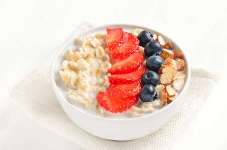 Oatmeal porridge with strawberry, blueberries and nuts in bowl