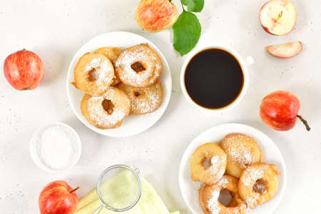 Apple rings on white plate. Cup of black coffee on light stone background. Top view, flat lay 스톡 콘텐츠
