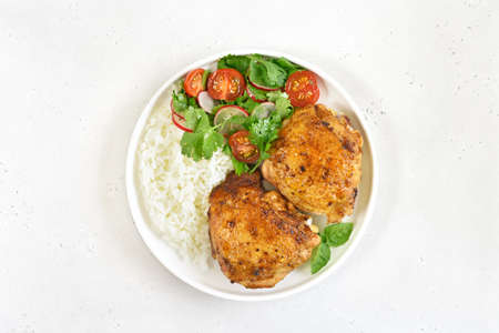 Fried chicken thighs with vegetables and rice in plate on white stone background. Top view, flat lay