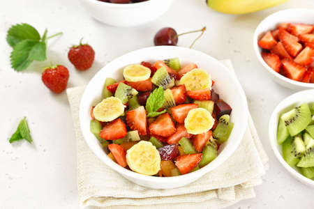 Healthy breakfast with fruit salad from strawberry, kiwi and banana on light stone background