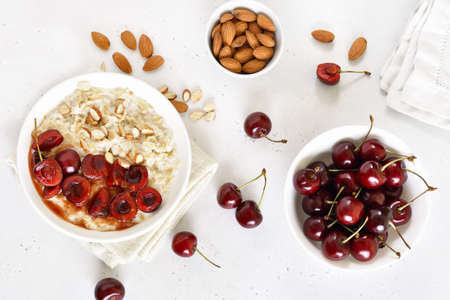 Oatmeal porridge with cherry slices and nuts in bowl over white stone background. Top view, flat lay