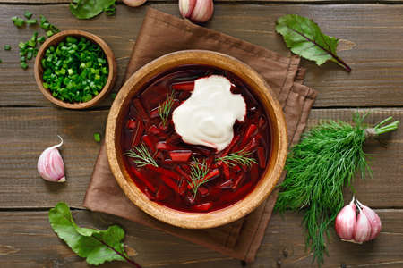 Traditional ukrainian russian soup (borscht) with sour cream over wooden background. Top view, flat lay