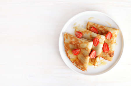 Crepes with strawberry and honey on white plate over wooden background with copy space. Top view, flat lay