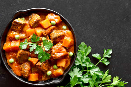Beef stew with potatoes and carrots in tomato sauce on black background. Top view, flat lay