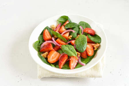 Healthy breakfast with fruit salad from strawberry, spinach and walnut. Close up view