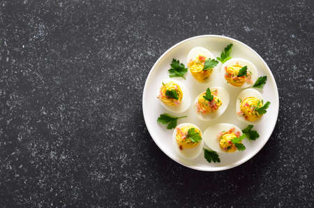 Deviled stuffed eggs with egg yolk, bacon, mustard and parsley on dark stone background with copy space. Top view, flat lay