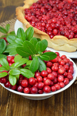 Ripe lingonberry in bowl and cowberry pie on wooden table