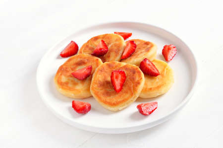 Pancakes with cottage cheese and strawberry slices. Healthy breakfast, close up view