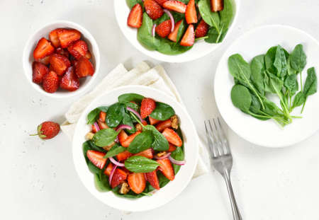 Salad with strawberry, red onion and spinach in white bowl. Healthy breakfast. Top view, flat lay