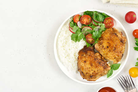 Fried chicken thighs with vegetables in plate on white stone background with copy space. Top view, flat lay 스톡 콘텐츠