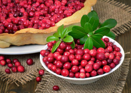 Ripe lingonberry in bowl and cowberry pie, close up view 스톡 콘텐츠